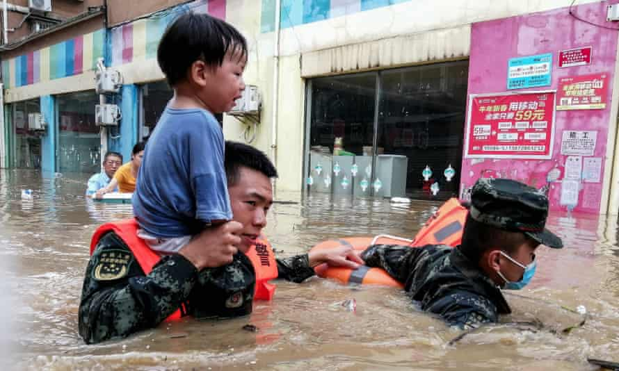 Rescuers evacuating a child from a flooded area following heavy rains in Suizhou, China.