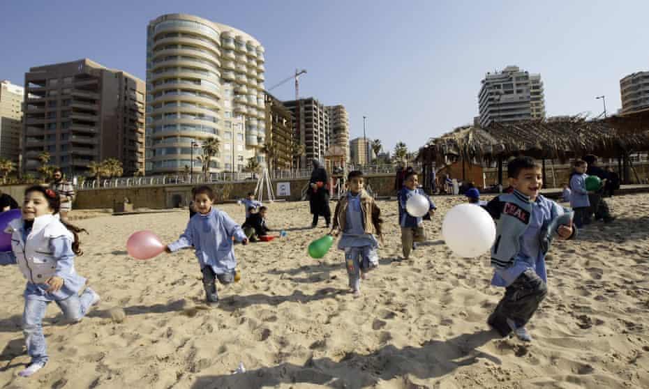 Lebanese school children run with the balloons on Beirut's Ramlet al-Baida beach on January 20, 2011