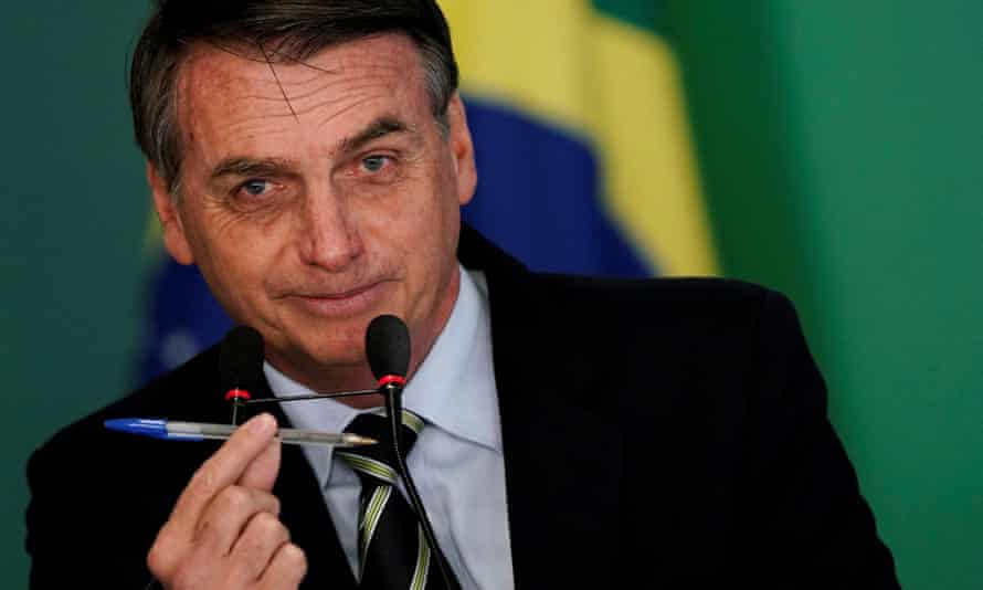 Brazil's president Jair Bolsonaro shows a pen during a signing ceremony of the decree which eases gun restrictions in Brazil on Tuesday.