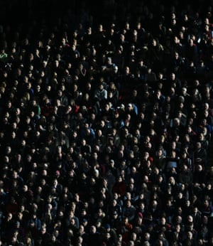 The autumnal sun lights the Aston Villa fans watching serenely in the stands.