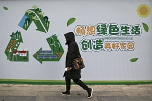 A woman in China walks past a recycling/environmental sigh