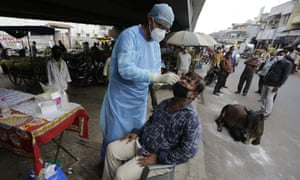 A health worker takes a nasal swab sample to test for COVID-19 in Ahmedabad, India on Friday