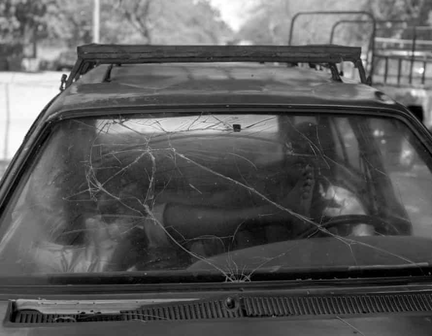 Two men rest in a badly damaged car.
