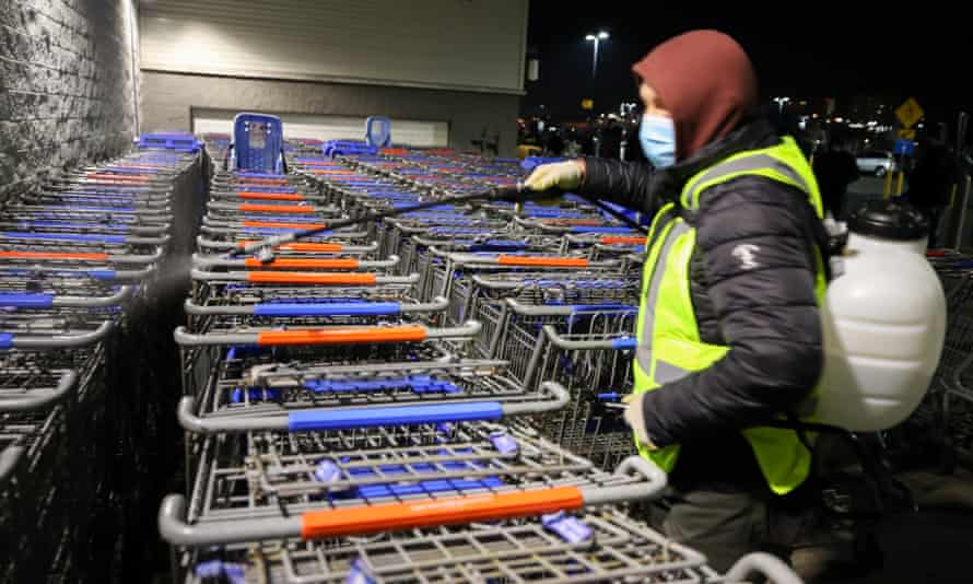 A worker sanitizes shopping carts as people line up in the early morning at Walmart on Black Friday.