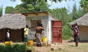 A woman drinks water at Makongeni village's water point, which was funded by Mikoko Pamoja's proceeds from trading carbon.