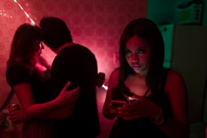 Elena checks her smartphone while Maria Fernanda dances with a boy at a party they have organised