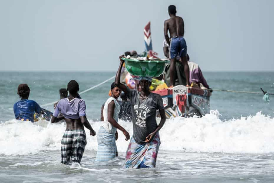 A woman brings in a bucket of fish in Gunjur village, The Gambia, in October 2018. Fishing culture has shifted as Chinese factories settled in three villages in the Gambian coast, making a deep impact in the ecosystem of the country. Photo: Xaume Olleros for The Guardian