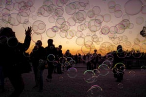 """Rome, ItalyTourists play with soap bubbles during sunset at """"Terrazza del Pincio"""" in the 'Eternal city'."""