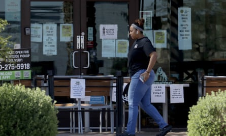 A person passes a temporary take-out only restaurant on Friday in Phoenix. Though many facilities are closed, the governor has not issued a shelter-in-place order.