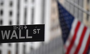 Wall Street sign with the US flag in the background