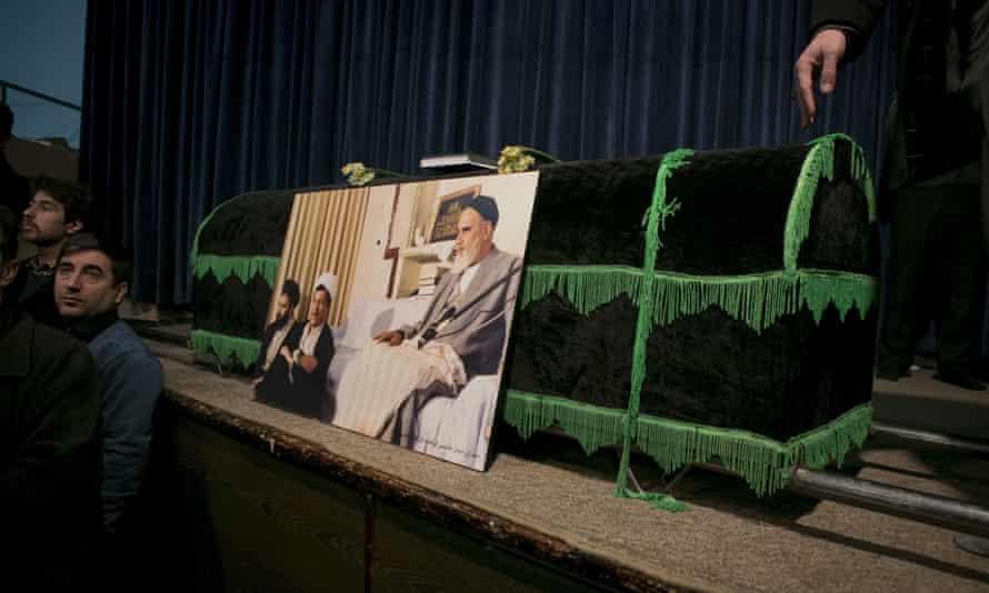 People mourn beside Rafsanjani's coffin.