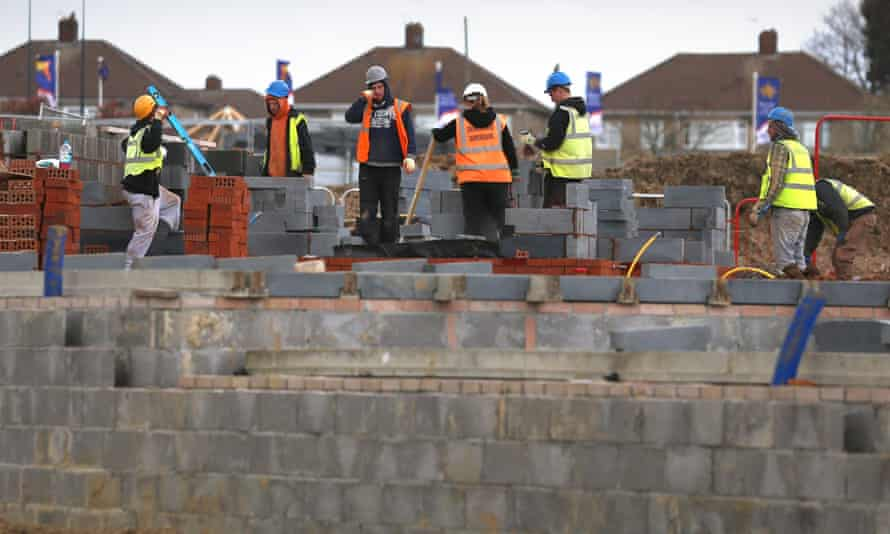 Construction workers build new houses on a housing development.