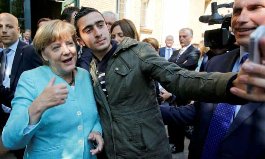 Anas Modamani takes a selfie with Angela Merkel in Berlin.