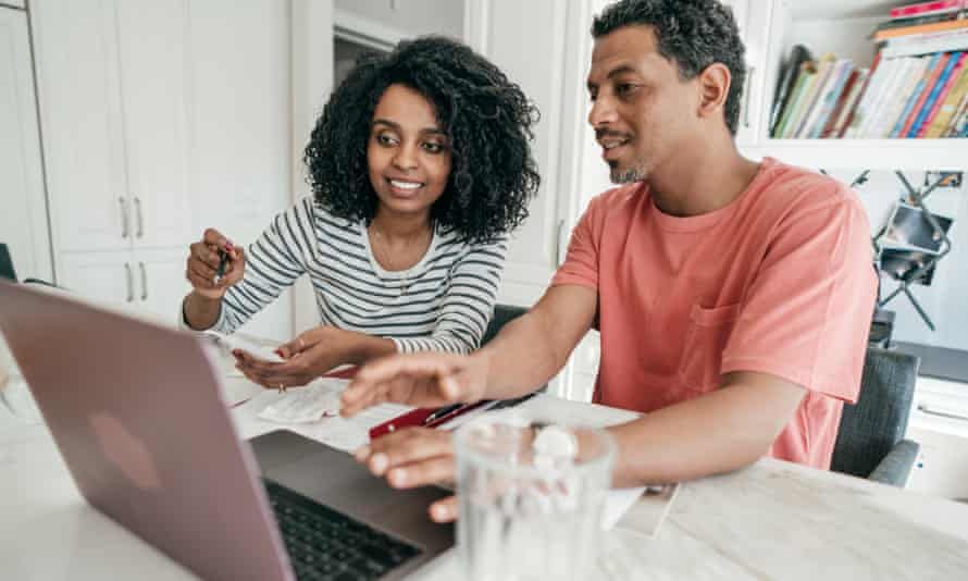 Couple and their financial planning in the kitchen with laptop