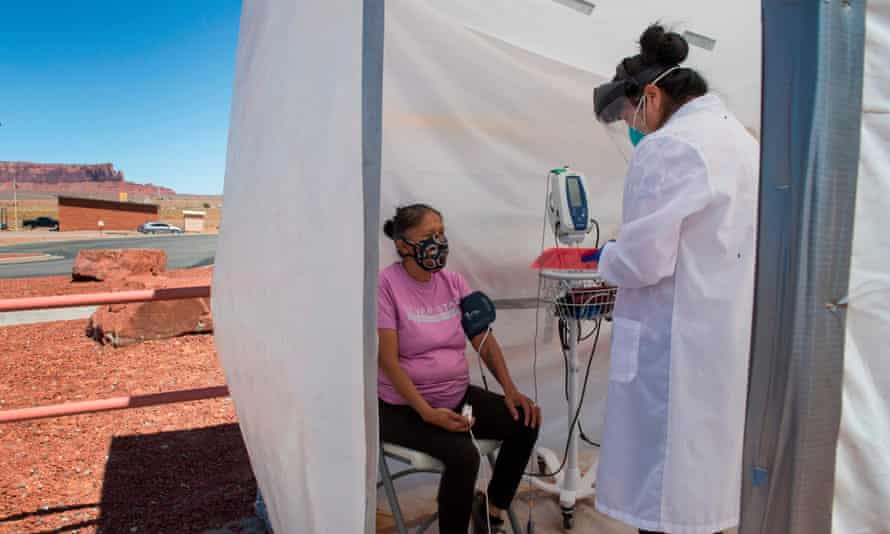 A nurse checks vitals from a woman complaining of virus symptoms in the Navajo Nation town of Monument Valley in Arizona, in May.