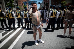 A man with traditional Japanese tattoos (irezumi), related to the yakuza, speaks on his smartphone