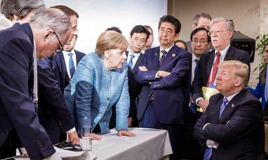 Donald Trump talking with Angela Merkel and surrounded by other G7 leaders during a meeting of the G7 Summit in La Malbaie, Quebec, Canada.