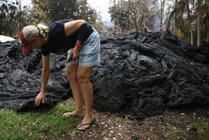 Stacy Welch inspects lava located next to her home, which remains standing, in the Leilani Estates neighbourhood in the aftermath of eruptions from the Kilauea volcano