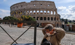 A tourist wearing a mask sits by the Colosseum in Rome on Monday, the day before the lockdown came into effect.