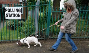 A woman walks her dog past a polling station