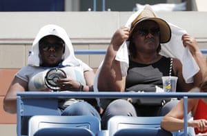 Fans try to escape the heat with a small fan and a towel as they watch Sloane Stephens play Anhelina Kalinina.