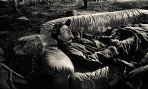 A homeless man sleeps out on a discarded sofa