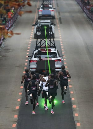 Eliud Kipchoge runs behind his pacemaking team following the timing vehicle which is projecting a green laser to guide them on the Hauptallee in Vienna on 12 October during his attempt to run a sub two-hour marathon.