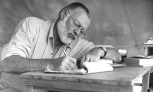 Hemingway works at a portable table while on a big game hunt in Kenya in 1952.