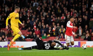 Arsenal's Reiss Nelson goes down after rounding Standard Liege's keeper Vanja Milinkovic-Savic.