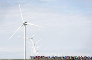 The peloton passes a row of wind turbines