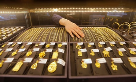 An employee arranges gold jewellery in the counter of a shop in Wuhan, China.