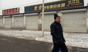 A man walks past shuttered businesses near the abandoned Fufeng steel plant in Tangshan which closed last year leaving 2,000 people out of work.
