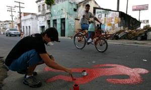 An activist paints the silhouette of a murder victim at the Coque slum in Recife, Brazil. The report's authors fear voters may look to strongman-style populists to solve the crisis.