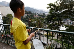 A boy taps his drumsticks on the rails looking over Rio from the hillside of Pereira da Silva