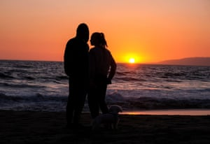 A couple watch the sunset on Venice Beach in Los Angeles, US