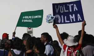 Rousseff supporters on the streets of Brasília hold signs in Portuguese reading 'Come Back Dilma' and 'The coup against Brazil'.