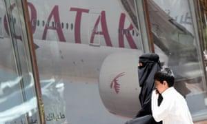 A Saudi woman and a boy walking past a Qatar Airways branch in the Saudi capital, Riyadh