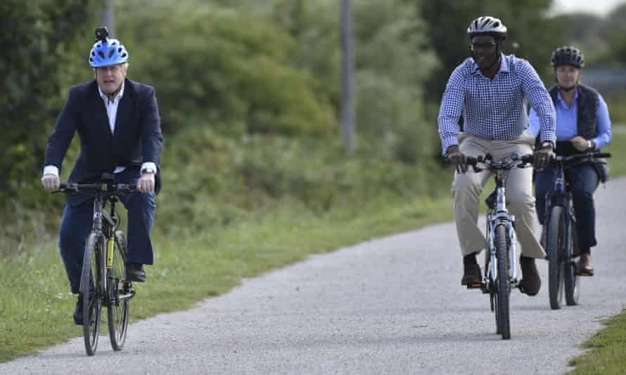 Boris Johnson with two others cycling along