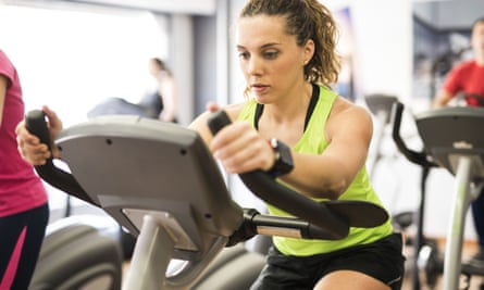 A woman training on an exercise bike in a gym