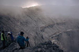 A technical assistant takes pictures of the interior of the crater