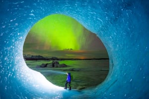 An ice climber stands in front of a large hole in Iceland's Vatnajökull glacier as the northern lights play in the background.