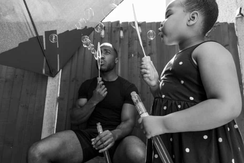Jordan and his daughter Callie blowing bubbles on a hot summer's day in the garden