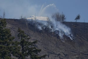A tanker truck sprays water on a persistent hotspot of a wildfire on a ridge, near Bonney Lake, Washington, south of Seattle
