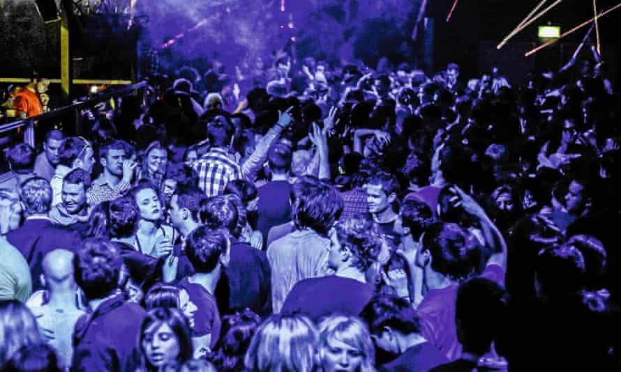 A throng of dancing clubbers lit by blue light, with a yellow spotlight picking out the DJ to the left of the picture