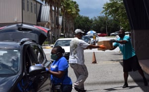 Volunteers distribute boxes of food from the Second Harvest Food Bank of Central Florida during a drive-through event at City of Destiny church on 6 July, 2020. The demand for food continues in the Orlando, Florida area due to the large numbers of service workers and others who have become unemployed due to the coronavirus pandemic.