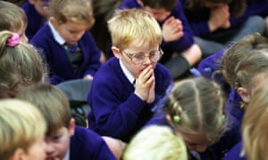 Children praying in assembly at a traditional Christian school