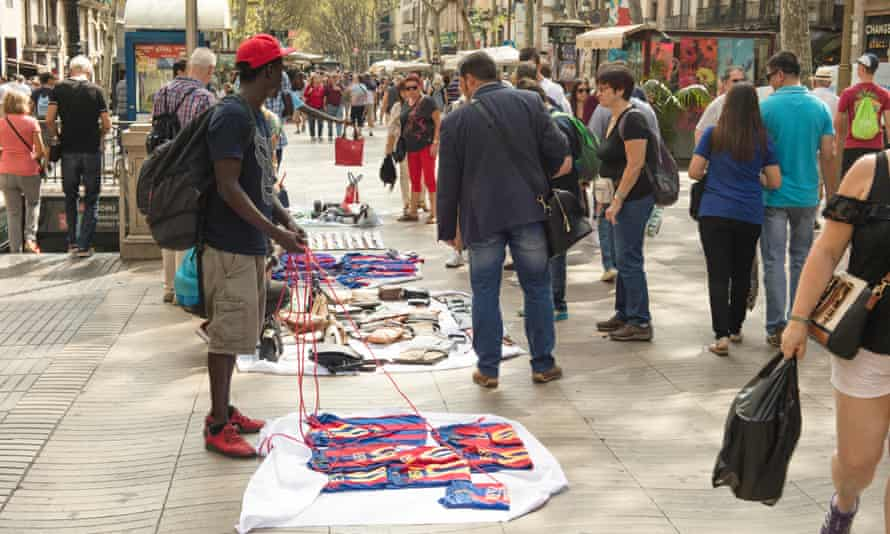Tourists look at the wares of the manteros in Barcelona, Spain.