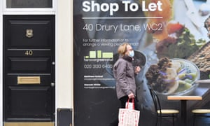 a masked man passes a shop to let in London