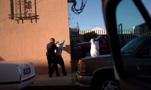 Los Angeles police department gang unit officers stop and frisk a gang member.
