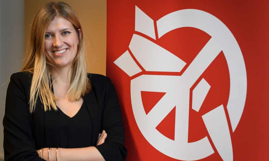 Beatrice Fihn, the executive director of the International Campaign to Abolish Nuclear Weapons poses next to the Ican logo